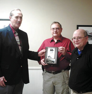 Gene and George Small (center, right) accept a plaque honoring their father from local Fraternal Order of Police president Bill Newman.