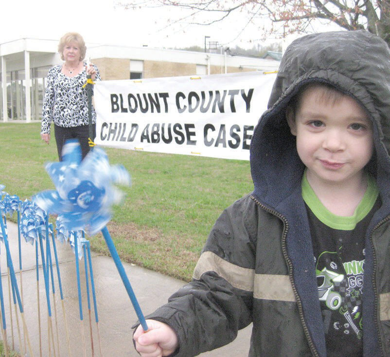 Ethan Howard of Oneonta, though not a victim himself, raises a pinwheel to commemorate the 140 children who were known victims of child abuse in Blount County in 2008. Jill Stansell, of the Blount County Children's Center, looks on in the background. Each pinwheel planted on the lawn at the Blount County Community Services Building represents a Blount County child abuse case. The occasion is April Child Abuse Prevention month. -  Ron Gholson