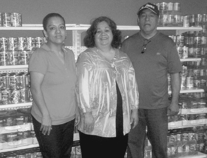 Pictured at the Blountsville Hispanic Church of God food bank are (from left) Cruz Cerventes, Emma Colunga, and Jesse Colunga.