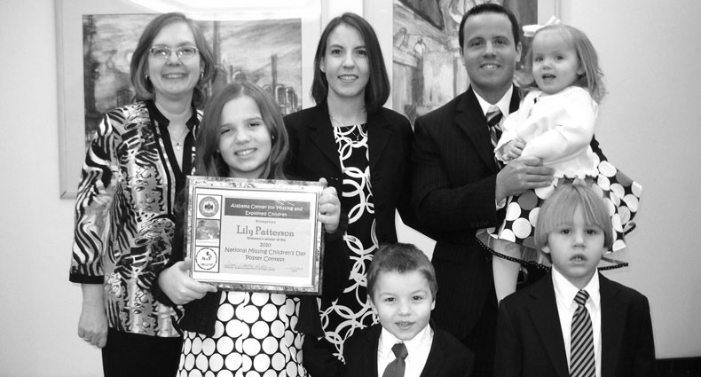 POSTER WINNER Lily Patterson displays the award she received. She is shown with her teacher Sonya Humber (back row, left); her parents Zondra and Tom Patterson, who holds baby sister Olivia; and brothers Caleb and Christian (standing beside Lily).