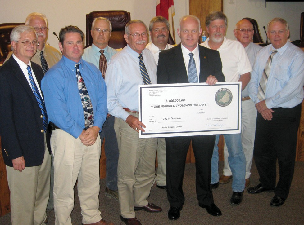 Blount County Probate Judge and Commission Chairman David Standridge presents a simulated $100,000-check to Oneonta Mayor Darryl Ray at the city's regular June 8 meeting. Pictured with the two are (front from left) Ralph Mitchell, Ed Lowe, Ray, Standridge, Tom Ryan, and Danny Robinson; (back) Tim McNair, Ross Norris, Mark Gargus, and Hal Buckelew.
