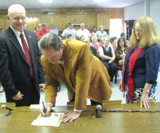 Probate Judge David Standridge, Mayor Jerry Jones with wife, Teresa Jones, signing the oath of office.