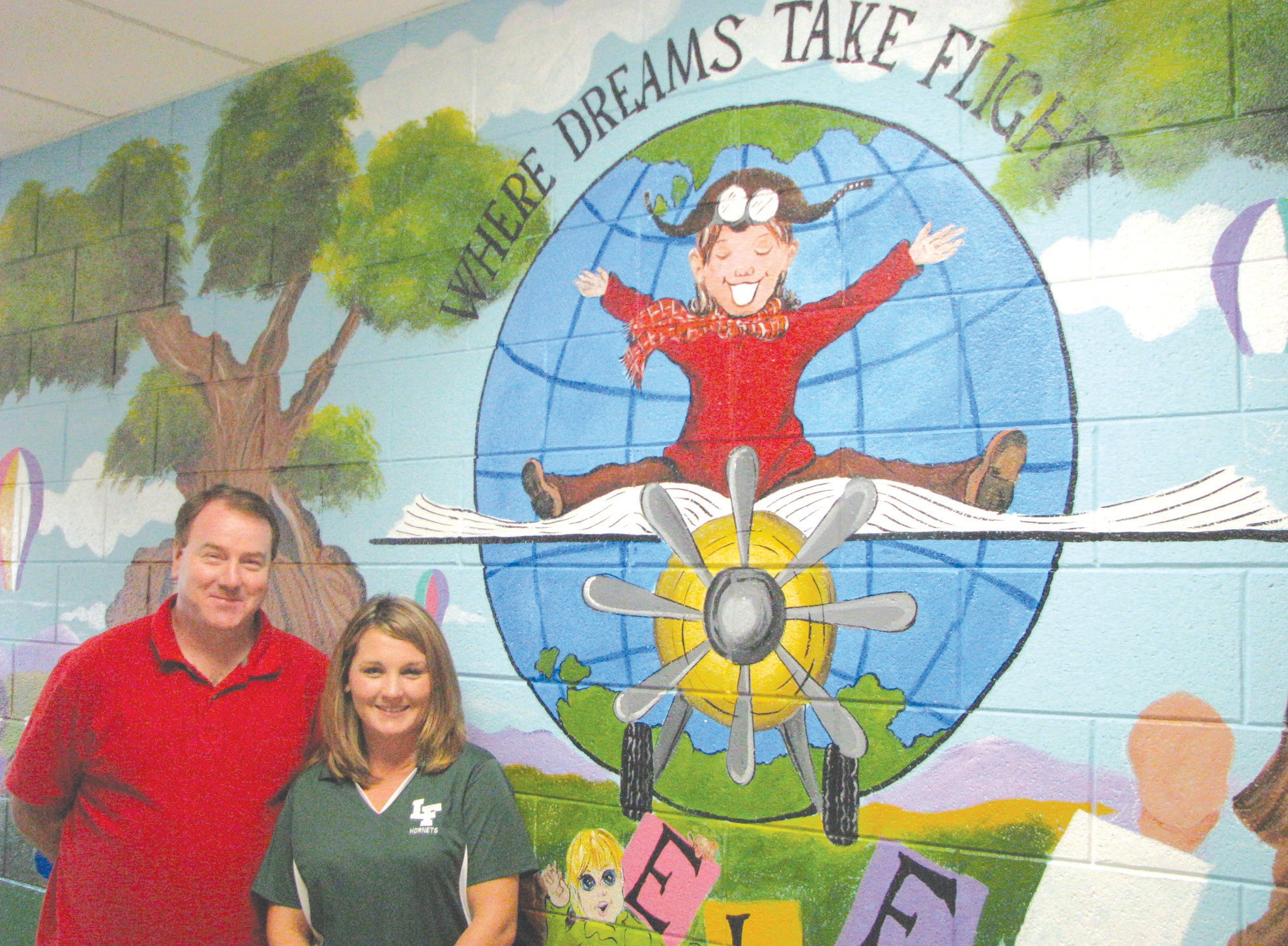 """Principal Amy Williamson and assistant principal Steve Love standing in front of Williamson's mural concept """"Where dreams take flight."""""""