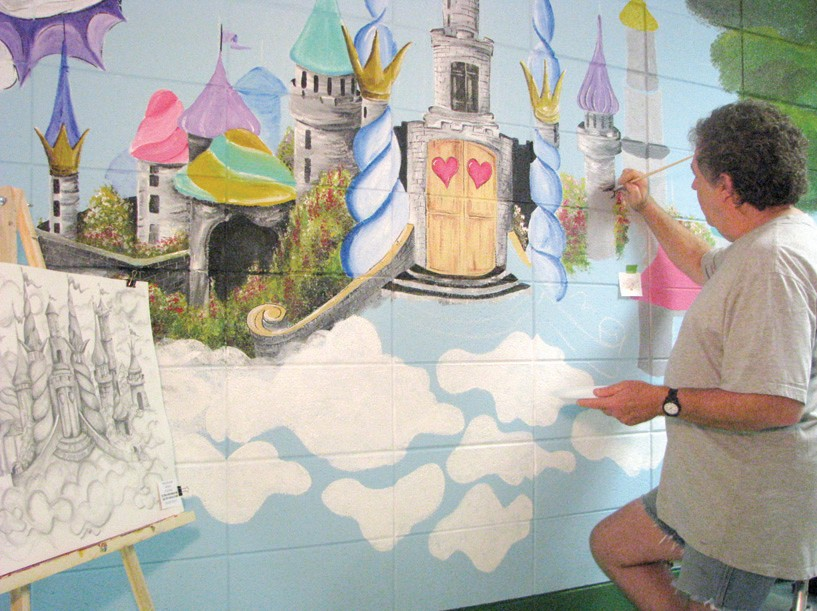 """Local artist and 1969 graduate, Jim Tidwell, unfolds his world of imagination, painting his concept that """"Reading takes you places."""""""