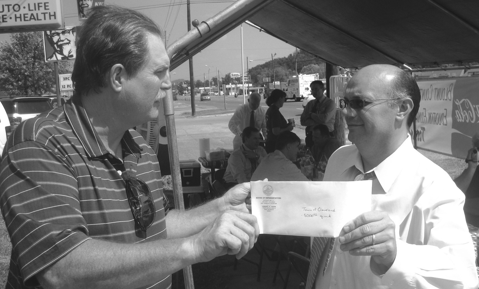 """Cleveland Mayor Jerry Jones (left) accepts a $5000 check from state Rep. Jeremy Oden, to be used to develop a dual-use youth football and soccer field in Cleveland. The field will be located just north of the city sewer plant on county road 1. Jones said excavation and site preparation work on the field will begin soon, with the aim of having the field ready for play by next spring or summer. """"We've got kids playing football and soccer on baseball fields, and that's certainly not ideal,"""" he said. """"This will give them a place of their own to practice and play,"""" he added. Oden said the money is a Community Service Grant from the state's general fund. Oden represents about a third of Blount County in a slice of territory lying along the northwest border, beginning at the Marshall County line and extending southwards to include both Blountsville and Cleveland. Both men were attending the Blount County Education Foundation radio-thon when the photo was taken. Jones is treasurer of the foundation and Oden is a regular supporter. – Ron Gholson"""
