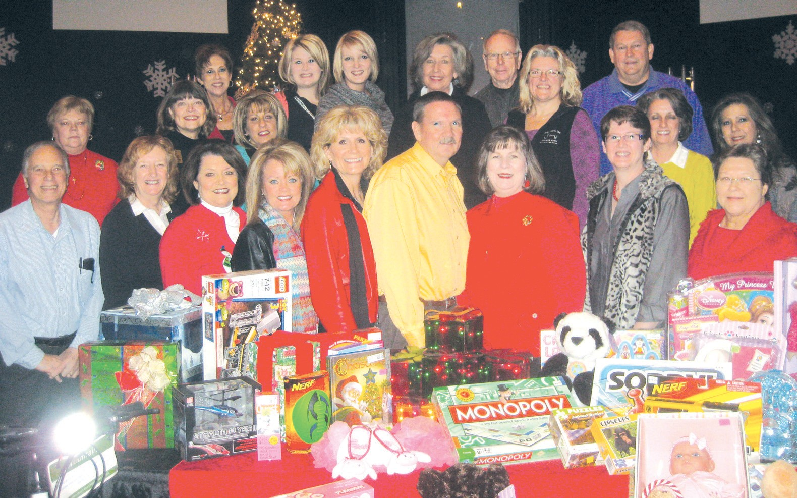 """Blount Real Estate Network members showed their Christmas spirit at a luncheon last week by playing Santa to six children whose wish lists were provided by Jerry Renno, Blount County Children's Center director (lower left corner). The result was the $1200 treasure trove of presents seen here, plus a bike that doesn't show up clearly in the photo. The presents were given to the Children's Center to relay to the children. Network members are Realty South, M&R Realty, and Blount Realty Team. They bought presents using proceeds from raffle tickets sold. Teresa Sloan, (fourth from left) accepted the $250 door prize on behalf of her daughter who bought the winning ticket. """"Blount County has been good to us, and we wanted to give back by bringing joy to some of its children who need it,"""" said a statement from the group. – Ron Gholson"""
