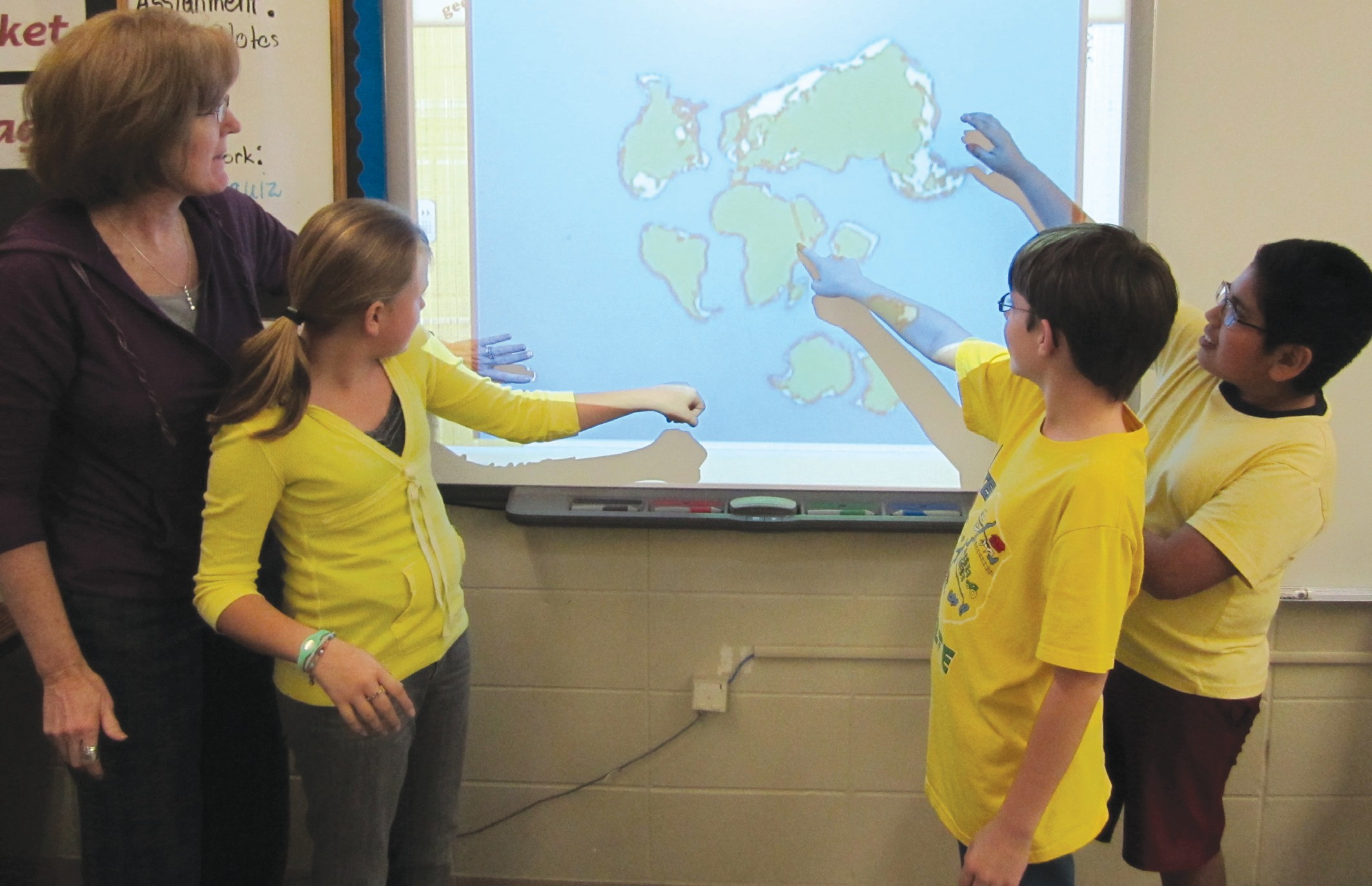 Cleveland sixth-grade teacher Claire Hornsby (from left) works with students Haley Shrewsberry, Tyler Washburn, and Luz Elizarraraz on a SMART Board showing an animated geography sequence. The sequence shows the separation over millions of years of the supercontinent Pangaea into the seven continents we know today. The boards are used to integrate all pictorial and textual material, including the Internet, to help students perform better in reading, math, science, and social studies. A cast of thousands (not literally) met after school Monday at Cleveland Elementary to celebrate a signal event: the school now has a SMART Board in every one of its 30-odd classrooms, representing an investment of some $66,000 over the last several years. Money for the sizable project came from several sources: the Blount County state Legislative delegation, educational grants, the Blount County Board of Education, CAWACO Resource Conservation and Development agency, and especially participation by Cleveland teachers, many of whom contributed their scanty classroom instructional supplies and technology funds for several years toward the project. CAWACO contributed $11,000 for the SMART Boards over the course of the project, including the final contribution, a $5000 check presented to the school earlier this week. Two teachers were singled out by Cleveland Elementary principal David Bradford for special recognition for their contributions to the project: second grade teacher Annette Protz and reading coach Linda Johnson. – Ron Gholson
