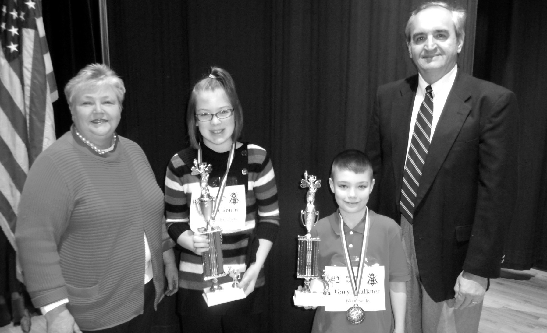 Gracie Coburn, sixth-grader at Oneonta Elementary School, won the 2011 Blount County Spelling Bee Feb. 8 in a spell-off at J.B. Pennington High School auditorium. The hotly contested event ran for 22 rounds and 80 words before Coburn was declared the winner after successfully spelling alcove. Gary Faulkner, a fifth-grader at Blountsville Elementary, was the runner-up. Also shown above are Jackie Sivley, new member of the Blount County school board, who served as one of the judges for the event, and county Supt. Jim Carr, who presented participants with awards honoring their accomplishments. Others working on the event included Stoney Beavers, Mitchie Neel, Donna Martin, and Cindy Williams of the Blount County Schools central staff and Craig Sosebee and Jessica Musso of J. B. Pennington High School. J.B. Pennington Ambassadors hosted and added a flair of class to the event in their snazzy black blazers.