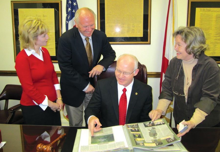 """Memorial Museum curator Amy Rhudy (from left), Dr. Charles Hendricks, Auburn University professor of veterinary medicine, Probate Judge David Standridge, and Auburn Heritage Association president Mary Norman confer over historical group's scrapbook as they discuss design of historical marker for upcoming dedication. The marker will designate the new drill field at Auburn's ROTC building as """"Major Max Morris Field,"""" named for the Blount County native who attended Auburn and played football there in the early 1940s and was killed in action in the Korean War."""