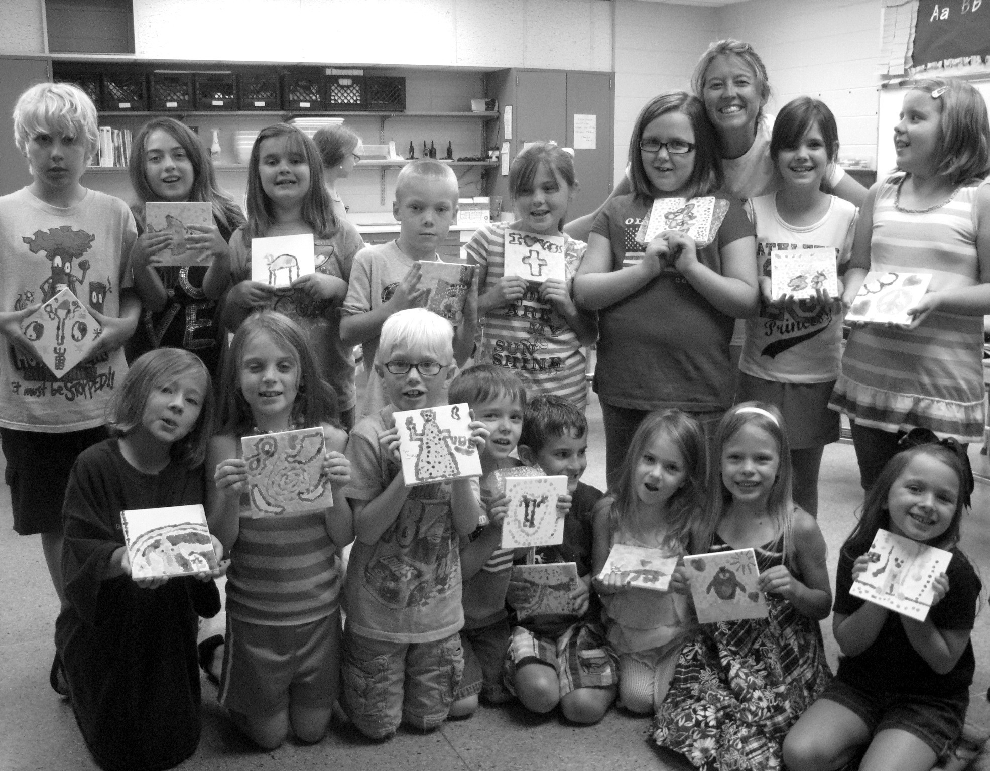 """Hayden students showing off their artwork created during the summer art program at Hayden Primary School are (front row from left) Kady Wood, Macy Lucas, Tyler Friday, Ryan Nix, Lex Sorensen, Emma Powell, Alexis Johnson, and Ella Armstrong. Back row (from left) Ben McGuire Davis, Sadie Odom, Hannah Sorrell, Logan Cox, Chloe Dover, Emma Nix, teacher Billie Miller, Leanne Brown, and Rayne Guerra. Art teacher/guidance counselor Billie Miller will teach after-school art classes at the school again starting in September. Miller chooses a curriculum based on student ability and adds, """"Basically, I create as I go, using the motto, I try, I will, I can."""" Children of all ages are welcome. For more information, contact her at bmiller@blountboe.net. – Tanna Friday"""