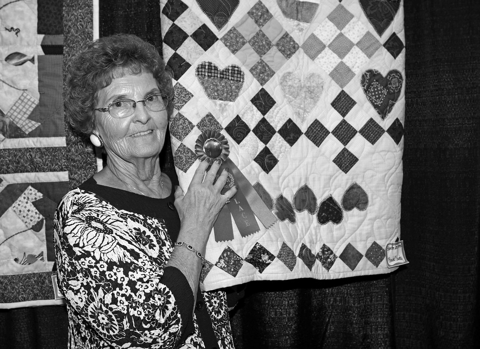 Blount County's Blanche Mitchell proudly displays her first-place winner in the machine-stitched quilt contest held Aug. 6 in conjunction with the Alabama Farmers Federation's conference at the Von Braun Center in Huntsville. An inveterate prize-winner with her creations, Mitchell placed second in the hand-stitched quilt contest. It was all part of the annual Cotton, Sewing and Quilting Contests and Tablescapes competition sponsored by the Alabama Farmers Federation Women's Leadership Committee.