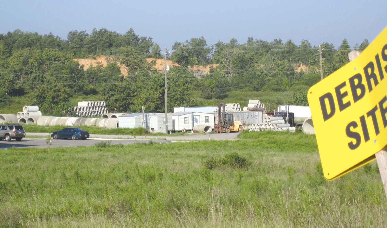 Site of landfill proposed by County Line lies off County Line Road, behind and to the south (left) of Concrete Pipe Supply LLC seen in foreground. Former strip mine highwall visible in background runs across the proposed landfill property. Sign in foreground directs trucks into entrance of WCA, a private landfill located across the County Line Road from the new proposed site.