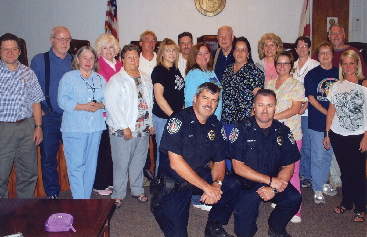 The 17 graduates of Oneonta's first citizen academy pose with Oneonta police lieutenant Steven Gunn and officer Mike Harris in the city's council chambers for their official photograph. Standing behind Gunn (kneeling, left) and Harris are (left to right) Joseph Huie, Tom Ledford, Joan Ledford, Diane Smith, Martha Holloway, Tony Hoeppner, Sheila Gargus, Jim Nelson, Sarah Earl, D.F. Payne, Mary Rushing, Sheila Marbut, Lori Stidham, Barbara Anderson, Dolores Johnson, Jay Johnson, and Kayla Wade.