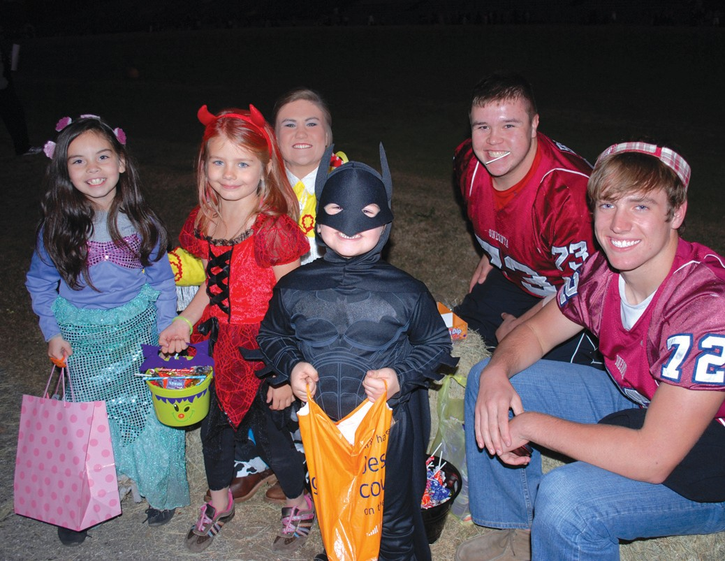 Cheerleader Haleigh Walden and varsity football players Blaise Brown and Blake Bean have fun sharing treats with costumed youngsters.