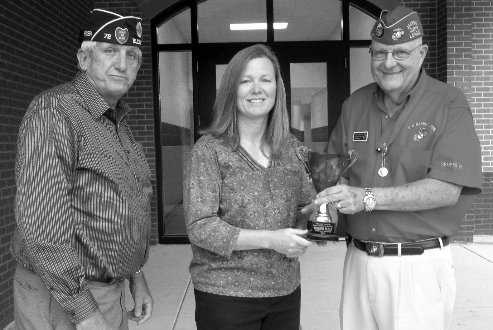 Rhonda Lindley (center), seventh-, eighth-, and ninth-grade science teacher at Southeastern School is presented the award for best float at the 2010 Veterans Day parade in Oneonta. Lindley and her students created a float showing an Apache helicopter for last year's event. (From left) Donnie Jackson, commander of American Legion Post 72, and Robert L. Venable, representing the Marine Corps League and Operation Grateful Heart, present the award. This year Lindley and her students will work on a float showing the Navy emblem, featuring an anchor, gun, eagle, Neptune's trident, and silhouettes of a battleship and submarine. The float is dedicated to Charles Weldon, Southeastern custodian, now retired from the U.S. Navy. The Veterans Day Parade is this Saturday, Nov. 5, at 10 a.m. Can't wait. – Ron Gholson