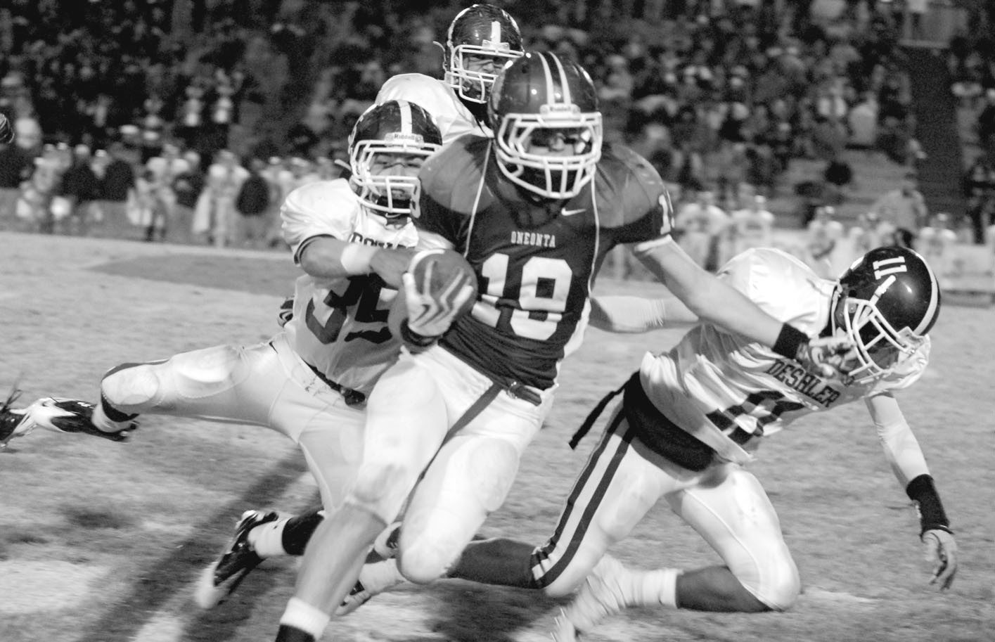 Oneonta running back Tyler Smith runs through a trio of Deshler defenders.