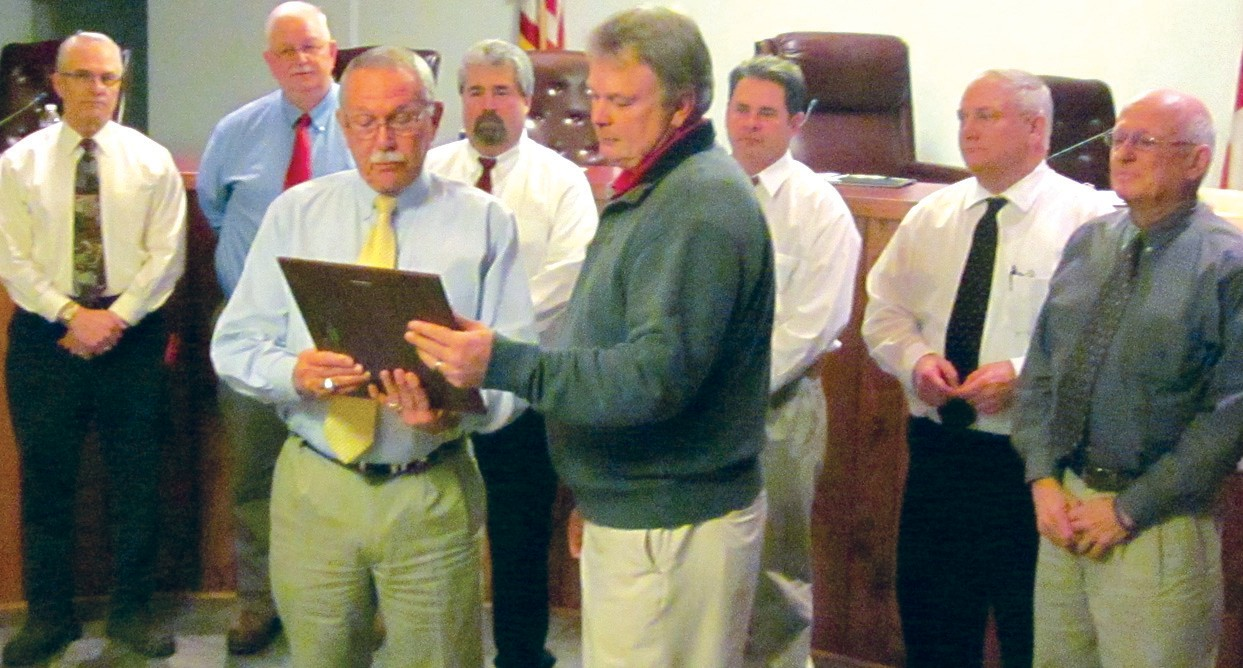 Oneonta Mayor Darryl Ray (foreground, left) presents a plaque to Oneonta High School head football coach Don Jacobs. Behind the pair are (from left) councilors Ross Norris, Tim McNair, Mark Gargus, city manager Ed Lowe, and councilors Danny Robinson and Hal Buckelew.