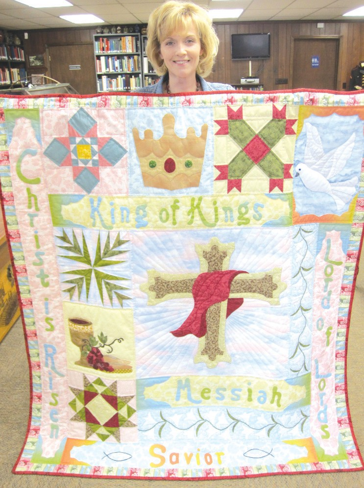"""The quilt of the month by that title, in celebration of Easter, is now on display in the window at Blount County Memorial Museum in Oneonta. Held for viewing by museum curator Amy Rhudy, the quilt was pierced, appliqued, and hand-quilted by Virginia Tidwell of Oneonta (right). As a charter member of the Quilters Guild, she is dedicated to passing along the art of quilting and sharing with others the satisfaction that comes from creating heirloom quilts. The centerpiece of the quilt is the cross, surrounded by blocks depicting the holy spirit (dove), Golgotha (stylized """"x""""), the crown, the temple court (geometric design in upper left corner), hosanna (palm fronds), and the Eucharist (the cup and bread). Emphasizing the overall theme are the appliqued words """"Christ is Risen,"""" """"King of Kings,""""""""Lord of Lords,"""" """"Messiah,"""" and """"Savior."""" – Ron Gholson"""