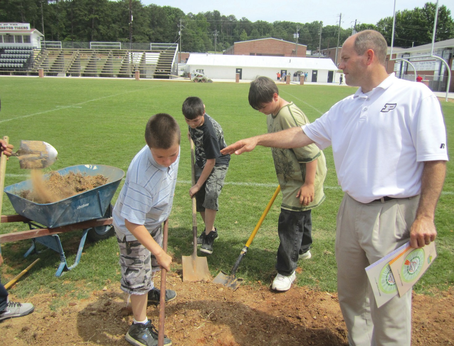 Dr. Philip Cleveland, principal of J. B. Pennington High School, is picured with seventh-grade students (from left) Joey Walden, Matthew Salinas, and Anthony Peek as they work on improvements to the school's football field.