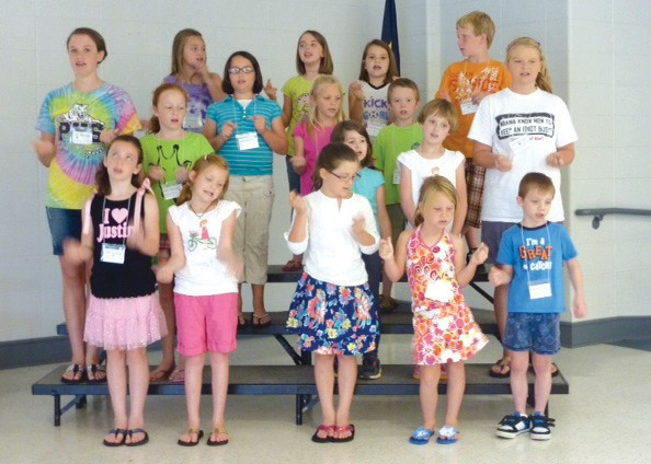 High schoolers, Kelsey Smith, far left, and Hannah Arnold, far right, sing along with elementary students at one of Expanding Horizon's music camps.