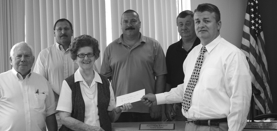 Dennis Beavers & Dicey Childers of the Blountsville Business Association jointly present the group's check for $10,230 to Town of Blountsville officials. The money is to be used to purchase 22 additional street lights. Front row from left: Councilman Ken Wilson, Childers and Beavers. Back row from left: Mayor Randy Millwood. Councilman Ken Mullins, and Councilman Michael Glass.