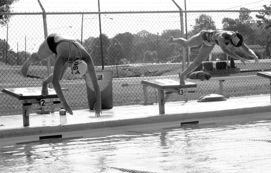 Grace Moody, age 16, and Ana Chappelle, age 11, dive in to their early morning practice Tuesday.