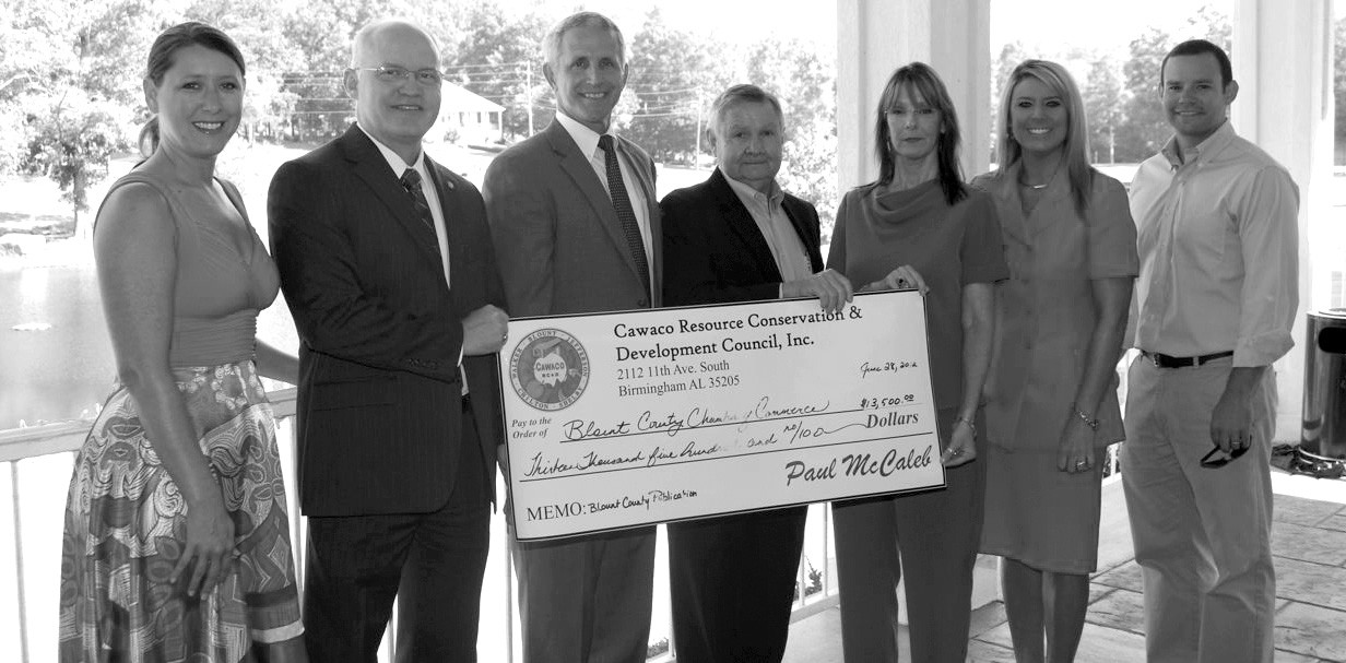 "From left, Aimee Wilson, David Standridge, Donnie Ray, Elwyn Thomas, Patti Pennington (CAWACO), Kelley Cochran, and Drayton Nabors (CAWACO) gather on the porch at Twin Oaks to highlight the Chamber's receipt of a $13,500 grant from CAWACO. The money will be applied to the cost of updating and printing the ""Welcome to Blount County"" magazine, also known as the newcomer's guide. The magazine is used as a recruiting tool for businesses, industries, and homeowners, as well as a reference source for residents. CAWACO Resource Conservation & Development is a 501(c)(3) organization that supports educational and community development projects in Central Alabama, with an outstanding record of assistance to county schools and communities. – Ron Gholson"