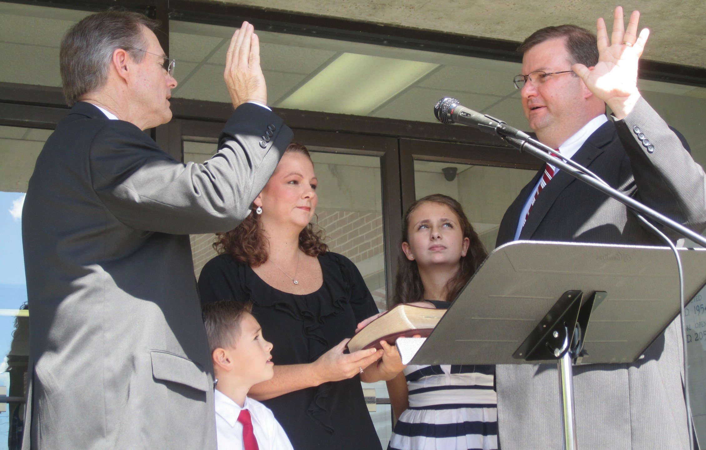 """Gregg Armstrong, known as county school board president and board member from Locust Fork/Cleveland (District 4), and as minister of music at Locust Fork Baptist Church, was sworn in as Blount County Revenue Commissioner Monday by Probate Judge Chris Green, sworn in himself less than a week before. Green had vacated that office after being appointed to assume the probate judgeship several months early by Gov. Robert Bentley. Shown are (from left) Green, Armstrong's son Charlie, 6, his wife Angie, daughter Hannah, 13, and Armstrong. Noting that it has been his privilege to serve two important groups of people in the county – those involved in school matters, and those at his church, he added, """"Beginning today, I get to serve all the people of Blount County,"""" vowing to serve """"with all my heart."""" Armstrong has been a member of the county school board for 20 years, serving as it's president since Jan. 11, 2011. He resigned from the school board in an emotional meeting just before the swearing-in. He will continue his avocation as minister of music at the church. He also owns a business, CATS Carbon, in Hayden. – Ron Gholson"""