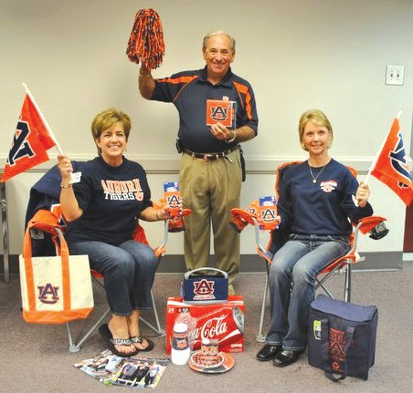 Prizes to be given away at the Radio-thon include Auburn and Alabama tailgate packages. Shown with various University of Alabama prizes – Front (from left) Conway Cleveland and Denise Martin. Back: Gregg Armstrong, Mitchie Neel and David Hamm. Pictured with Auburn University prizes are Becky Hicks, Jim Henderson and ShaRonda Holmes.