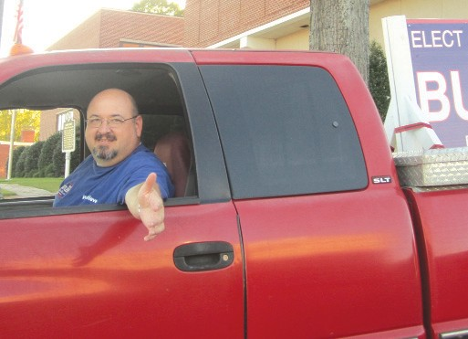 Mark Butler greets constituents in his 'old farm truck,' converted to a campaign battle wagon.