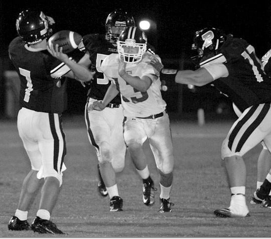 J.B. Pennington quarterback Brandon Butts releases the ball as Locust Fork's Nick Long applies pressure.