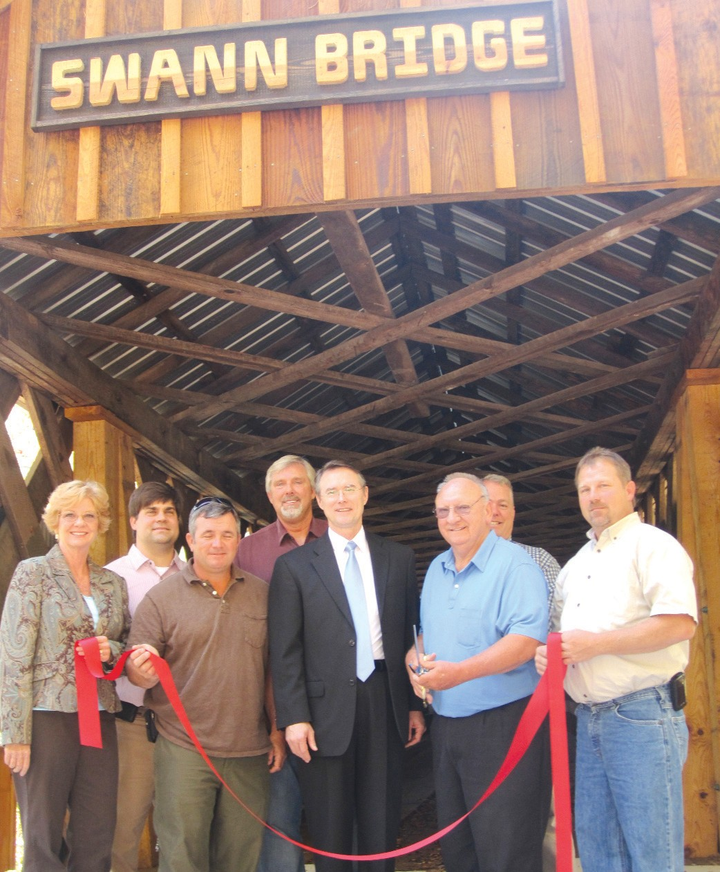 The photo shows the group that helped bring the covered bridge renovation project to completion. They spoke briefly at a ceremony at Swann Bridge Monday as two of the bridges – Swann and Easley – were opened to traffic. From left: Sharon Murphree, Friends of the Covered Bridges of Blount County; Winston Sitton, county engineer; District 1 Commissioner Allen Armstrong; Barry Johnson, Friends of the Covered Bridges; Chris Green, probate judge/commission chairman; Bob Smith, president of Bob Smith Construction Company of Trussville and Blount County native, the only contractor to bid on the project; John Friedberg (partially hidden) project manager for Bob Smith Construction; and District 3 Commissioner Dean Calvert.