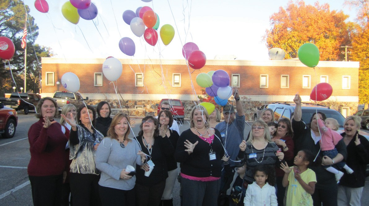 Balloons fly skyward from the Department of Human Resources office in Oneonta to celebrate National Adoption Day, set for Nov. 17. Front row from left: Maria Dresser, DHR Director; Cheryl Helton, program supervisor; Bethany Valdez, foster care supervisor; Debra Cheek, adoptive resources caseworker; Vonda O'Bryant, caseworker; and adoptive parents and adopted children of Blount County.