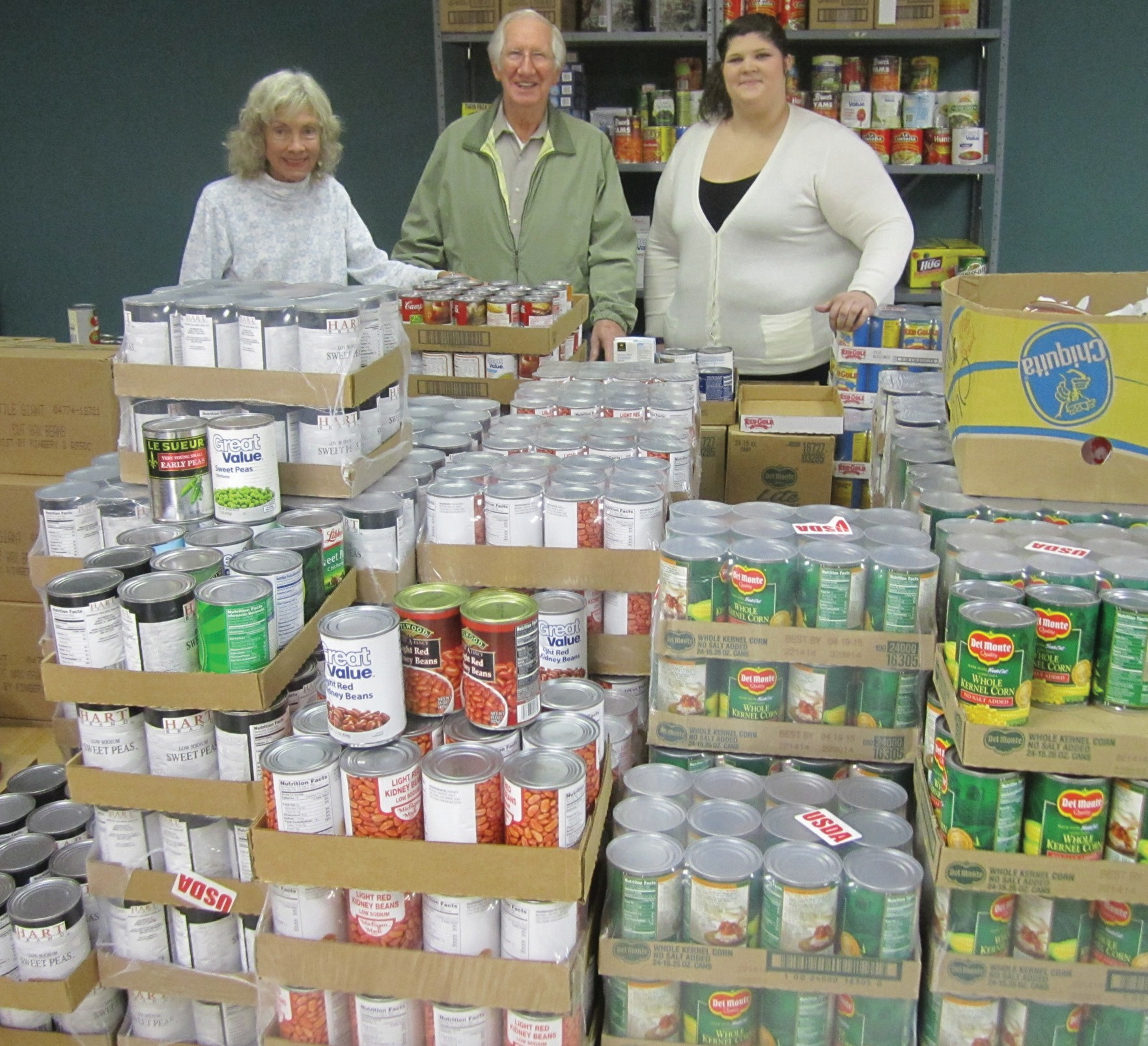 Food workers Anne Barnes (left) and Bethany Taylor survey the food bank pantry with Hope House director Bud Jones.'Giving is the best this year it's ever been,' Jones said,'and the economy is at its worst.'