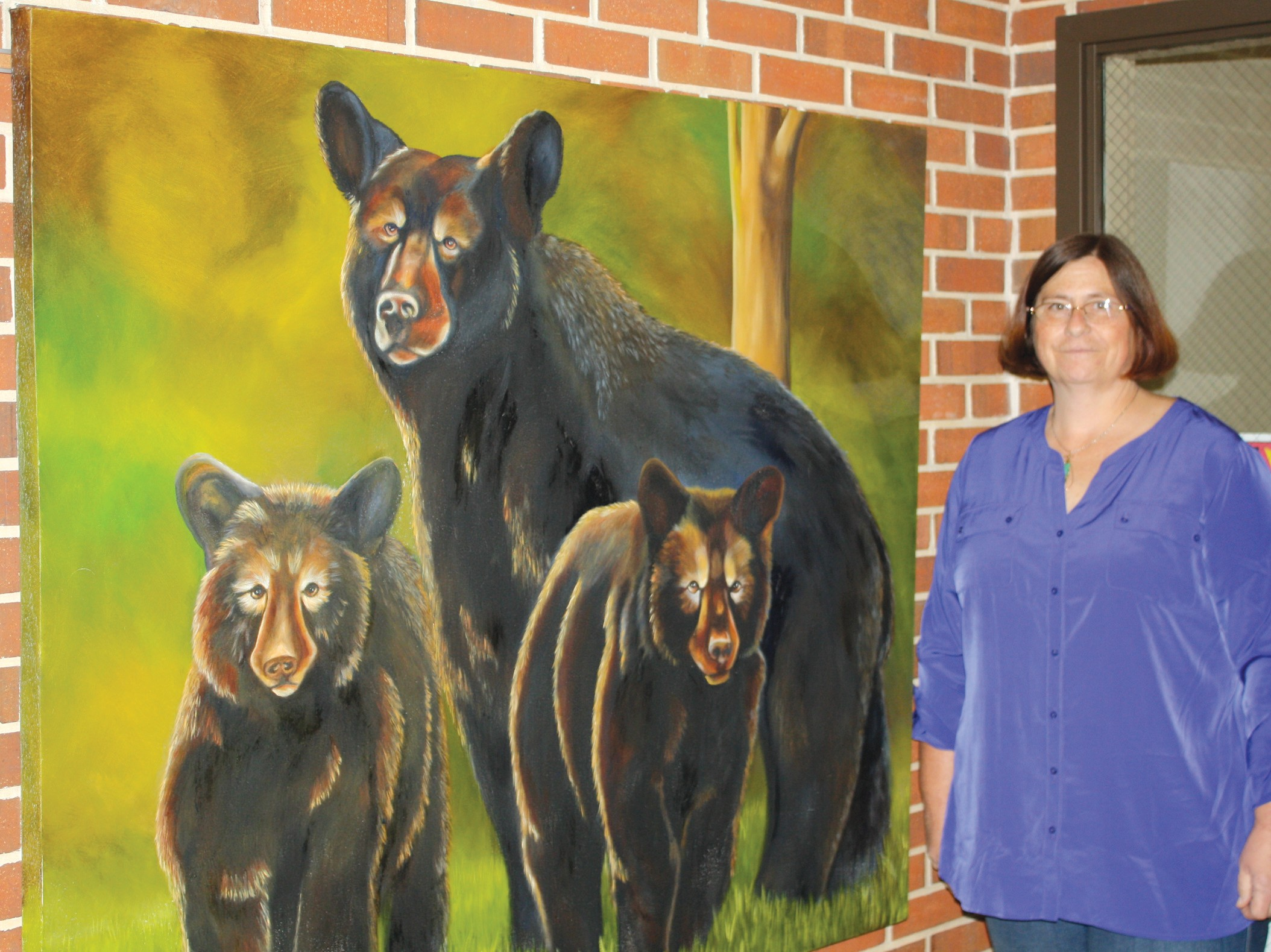 Trish Priest with her painting of a bear and her cubs. Priest took various pictures of the bear family during her vacation and decided to transfer one photo to a painting.