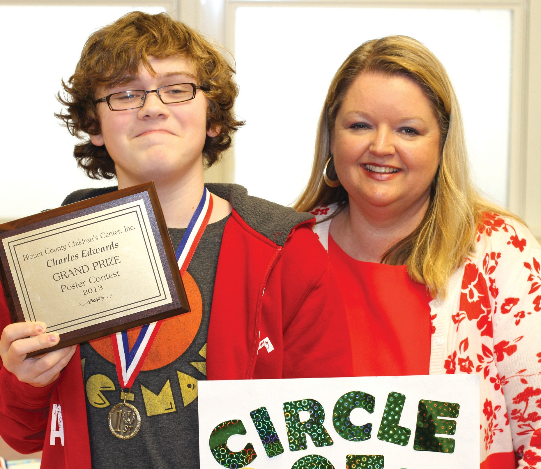 "Charlie Edwards of Southeastern School was the overall grand prize winner in the Blount County Children's Center's annual poster contest. The reception for winners in each grade was hosted by District Judge Sherry Burns. As shown above, both were proud of the outcome. His poster's theme was ""Circle of Safety."" It showed all the trustworthy people – parents, teachers, preachers, policemen, counselors, and others – a child can trust with a dark secret like child abuse. Facts on child abuse – 99 abuse cases last year in Blount County – 90 percent plus were female children. All were abused by a family member, relative, or well-known acquaintance. In over 15 years of dealing with child abuse, no cases recalled by the staff of abuse by a stranger, according to executive director Jim Ed Clayton. Bad news: already 50 reported cases this year, well above last year's average for this time. Good news: you can fight abuse by supporting the Children's Center (and having a wonderful evening to boot) at its April 23 fundraiser: Three on a String and Gadsden's Kate Falcon singing and a Lee Alexander meal at World Outreach Center at 6 p.m. Just $32 per person for entertainment, program, and meal. Call the Children's Center or a board member for tickets. – Ron Gholson"