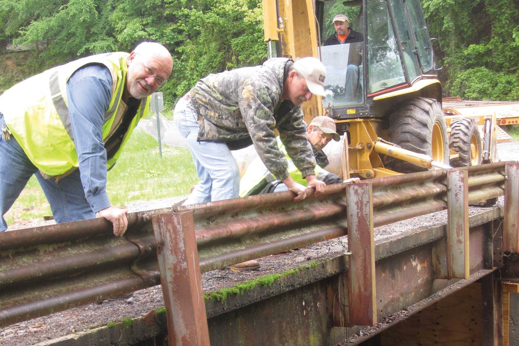 District 4 crew, from left, Commissioner Gary Stricklin, foreman Rob Branham, Rodney Burns, and David Gargus (in loader) work on bridge over Beech Branch on Horton Mill Road. They rebuilt abutments to the bridge, repaired the guardrail, and were reinstalling it the morning this photo was taken. The guardrail on the other side was missing and will be replaced, too.
