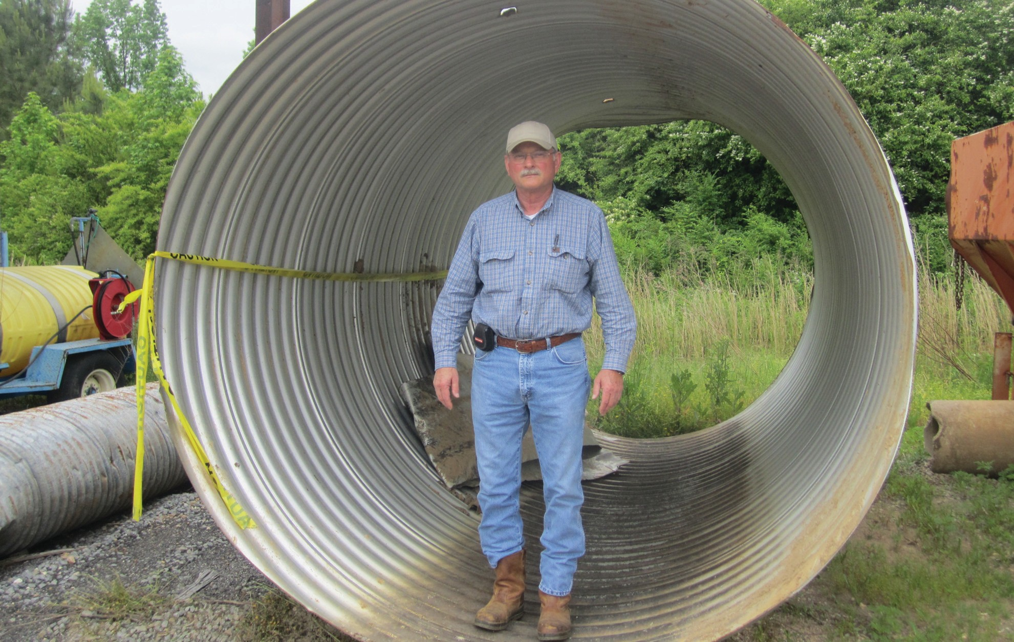 District 2 Commissioner Carthal Self demonstrates one of his district's bigger recent problems: a 100-foot run of 96-inch diameter pipe – all of which had to be replaced except this one section. The rest of it had rusted through and had to be pulled out. Cost: $14,000 plus (just the pipe). Time required for the replacement project: roughly two weeks. The ditch on Mt. Carmel Rd. had to be re-routed and the pipe reburied. Works fine now, Self said.