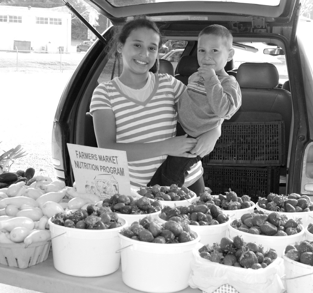 Karla, age 11, and Noah, age 2, help their mother, Elvira Lopez, who sells produce for Jerry Marsh Farms at the Farmer's Market located at the Blount County- Oneonta Agri Business Center.