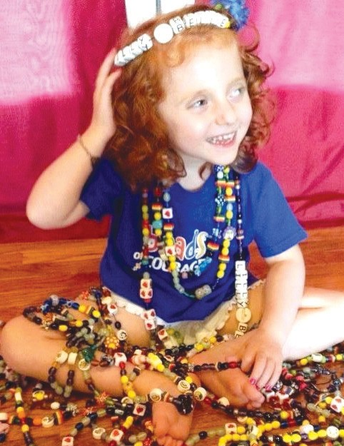 Lilly Belle suffered from a rare disease known as MIOP. Here she is pictured with Beads of Courage, handblown glass donated to hospitals with terminally ill children. Each bead is earned after the child endures a procedure for their treatment.