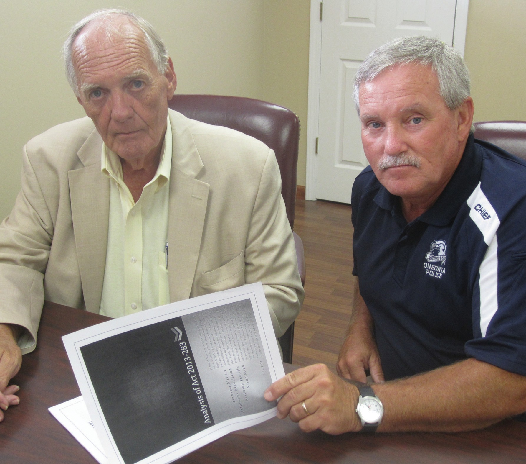 Blount County Sheriff Loyd Arrington and Oneonta Police Chief James Chapman confer over a copy of a conference handout analyzing the impact of Alabama's new Gun Law which went into effect Aug. 1.