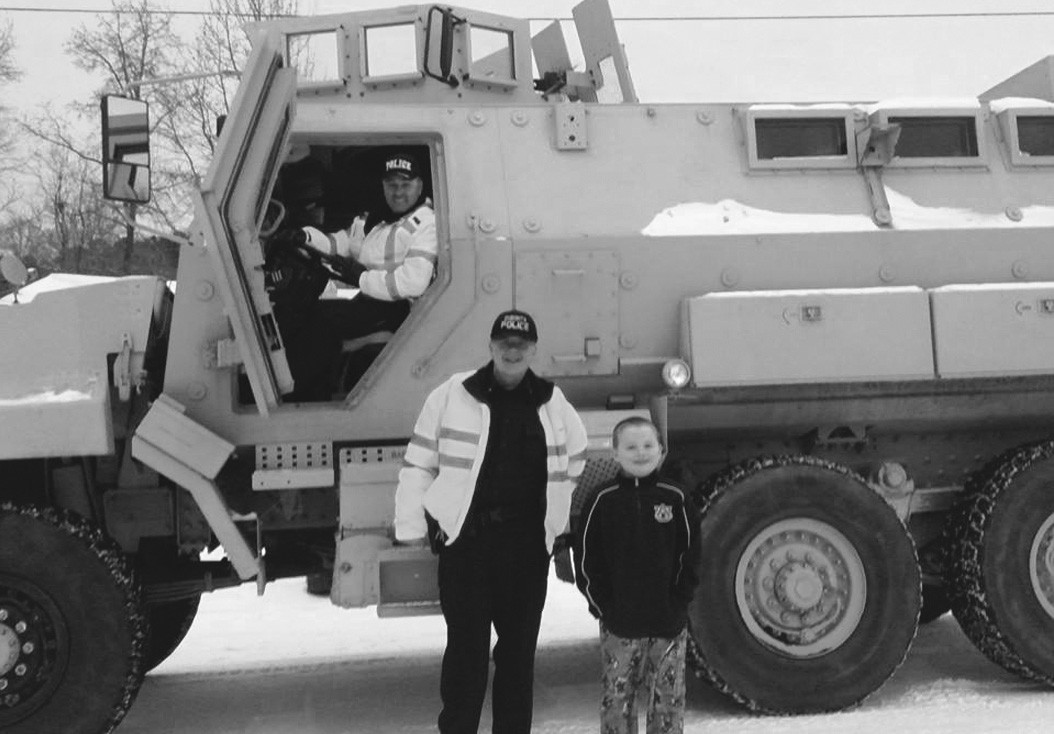 It's an MRAP. M-Rap. Stands for Mine Resistant Ambush Protected vehicle. Driving the ride is Oneonta patrolman Mike Harris. Helping show it off is patrolman Scott Evans, assisted by son Matthew. The vehicle helped withstand an ambush last Tuesday, in the form of a stealthy, sneak-attacking winter snowstorm. It's on loan to the Oneonta Police Department. It was used to transport children home when one bus failed to complete its appointed rounds in last week's winter surprise.