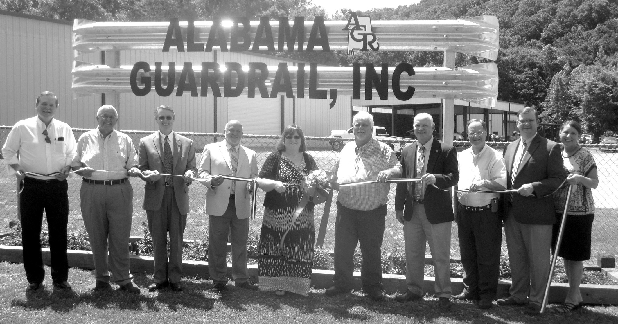Officials gather to celebrate the grand opening of Alabama Guard Rail last week. From left: Cleveland Mayor Jerry Jones; Economic Development Council chairman Clyde Woods; Probate Judge Chris Green; District 4 Commissioner Gary Stricklin, company president Catherine Huff; company vice president Keith Dillard; Rep. David Standridge; Rep. Randall Shedd; Blount County Revenue Commissioner Gregg Armstrong; and Blount County-Oneonta Chamber of Commerce executive director Aimee Wilson. Most played a role in the company's relocation to the former Robertson property on U.S. 231 near the eastern town limits of Cleveland. The company, with 43 workers, many with strong Blount County ties, moved from its former location to escape periodic flooding of shop and offices at its site on Turkey Creek in Pinson. Alabama Guard Rail supplies roadway guard rails and provides installation throughout Alabama and part of Mississippi. The event was an unusually large grand opening, with more than 100 well-wishers present, many if not most, with personal ties to the company, its owners, and/or its employees. 'We want to be a helpful part of the community. However we can help, we want to do,' Huff said. – Ron Gholson
