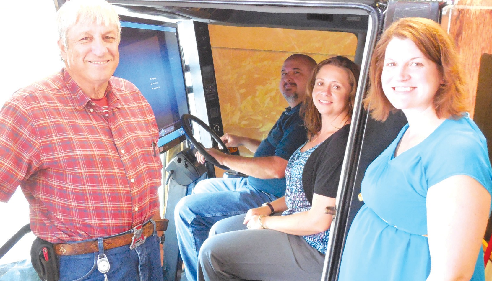Aboard the Ag in Action mobile learning lab cotton picker (from left to right) are Jimmy Tucker, soil conservation technician with the Natural Resource and Conservation Service (NRCS); Mark Butler, watershed coordinator with the Soil & Water Conservation District (SWCD); Polly Morris, district administrative coordinator with SWCD; and Merry Gaines, district conservationist with NRCS.