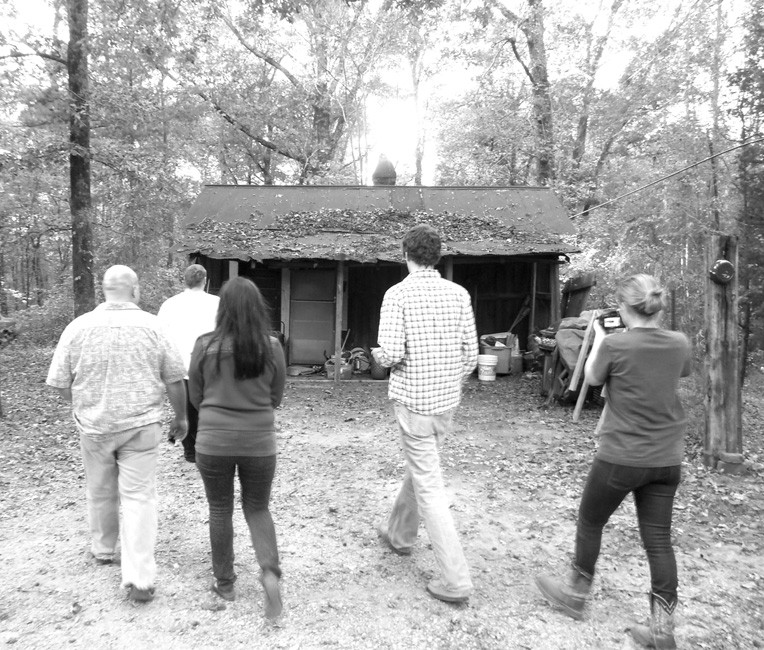 Staff from WCRL and Alpine Advertising walk to an abandoned slave house.