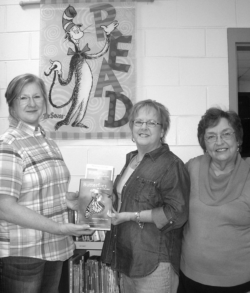 Oneonta Elementary School Librarian Denise Turner accepts the book, Butterflies of Alabama: Glimpses Into Their Lives, from Rose Garden Club members Nell Gibbs and Sue Tidwell.