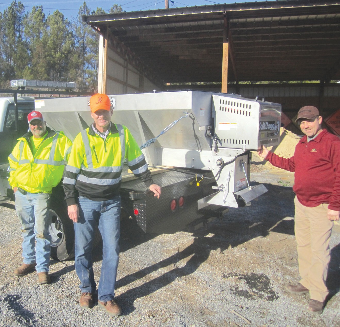 District 3 workers show off shiny new spreader which has just been mounted on a flatbed truck for use this winter. From the left, mechanic David Kemp, foreman Jimmy Hicks, and District 3 Commissioner Dean Calvert.