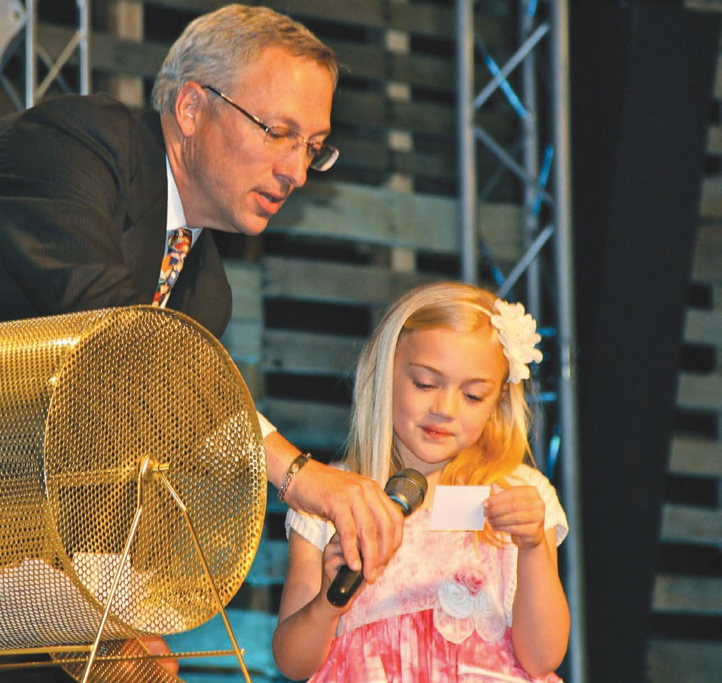 Jim Ed Clayton assists Lydia, age 7, daughter of Jimmy and Mitsy Sewart, with last year's door prize drawing.