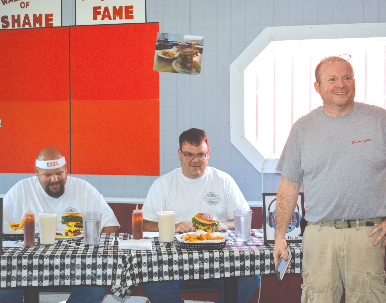 Stephen's Diner owner Stephen Hill welcomes the latest challenger's to his Triple- Bacon Cheeseburger Challenge – Jeremy Lesley (left) of WCRL and Jeremy Hyde of Alabama Power. Despite a big cheering section for each, the pair were ultimately unable to down the triple cheeseburger, homemade potato chips, and 32-ounce milkshake in the 20 minutes allowed. A gutsy effort, in more ways than one. –Rob Rice