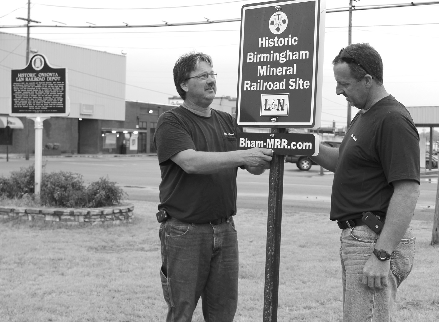 Last Friday, Oneonta park and recreation employees Norman Clements, left, and Chad Weems installed the Historic Birmingham Mineral Railroad Site sign in front of the Oneonta Public Library. As a part of Birmingham native James Lowery's project, signs are being placed at locations included in the 156-milelong Birmingham Mineral Railroad which ran from 1884-1988. For more information, visit www.bhammrr.com. The Blount County Memorial Museum assisted in the sign placement. – Nicole Singleton